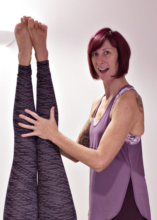 Michele Ross assisting a student in headstand